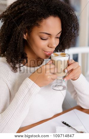 Young woman is drinking latte.