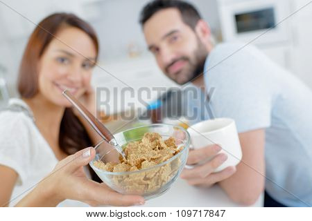 Couple having breakfast, showing bowl of cereals