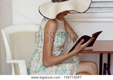 The girl in white hat reading a book. Bible reading woman.