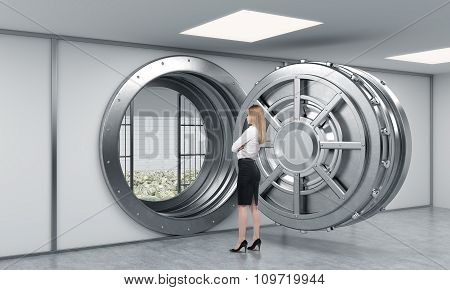 Young Lady Standing In Front Of A Big Unlocked Round Metal Safe Full Of Money In A Bank Depository W