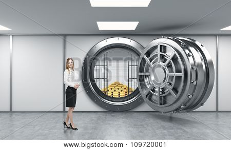 Young Lady Standing In Front Of A Big Unlocked Round Metal Safe In A Bank Depository With A Pyramid