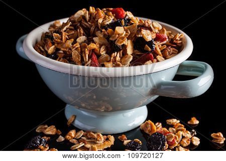 Granola in a bowl on black from side