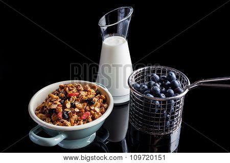 Blueberries granola and yogurt on black high angle
