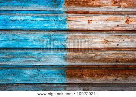 Weathered plank background half painted in blue color