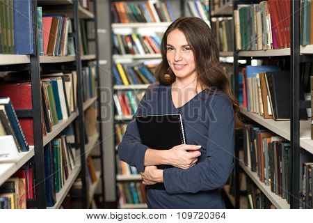 Smiling Young Lady With Long Dark Hair Standing And Holding A Black Copy Book Between Book Shelves I