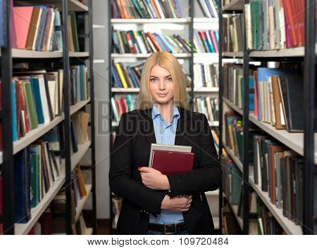 Smiling Young Lady With Loose Long Blonde Hair Standing And Holding Two Book Between Book Shelves I