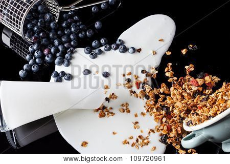 Yogurt blueberries granola mixed on black high angle