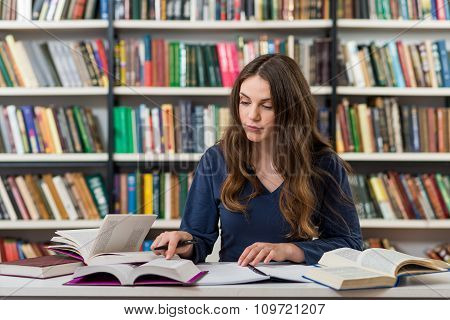 Serious Young Girl With Loose Long Dark Hair  Sitting At A Desk In The Library With An Open Note Boo
