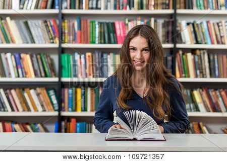 Smiling Young Girl With Loose Long Dark Hair  Sitting At A Desk In The Library With An Open  Book, L