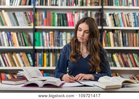 A Young Brunette Girl Who Is Sitting At A Desk In The Library With An Open Note Book Writing Out Inf