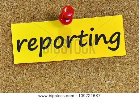 Reporting Word On Yellow Notepaper With Cork Background