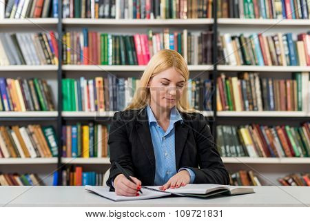Smiling Young Girl With Blonde Hair  Sitting At A Desk In The Library With An Open Note Book Making
