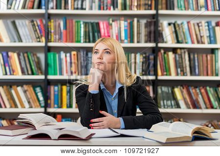 Smiling Young Sitting At A Desk In The Library With An Open Note Book And Book Around,  With Chin O