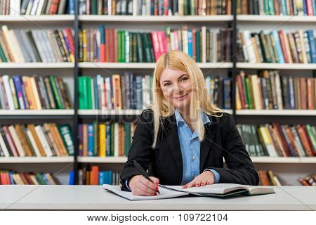 Smiling Young Girl With Loose Blonde Hair  Sitting At A Desk In The Library With An Open Note Book W