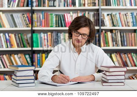 Serious Young Man With Dark Hair Sitting At A Desk In The Library With An Open Note Book, Writing, P