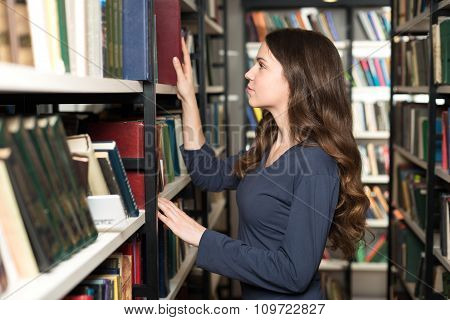Young Lady With Loose Long Dark Hair Choosing A Book Between Shelves In The Library, Touching A Book