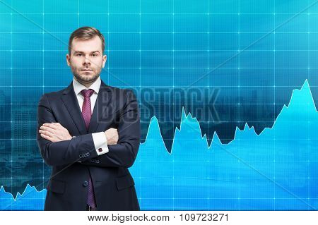 Businessman With Hands Crossed Standing In Front Of A Blue Graph Demonstrating Growth, Fluctuations,