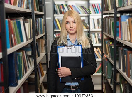 Smiling Young Lady With Loose Long Blonde Hair Standing And Holding A Note Book And A Note Pad Betwe