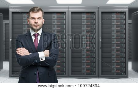Young Man Standing With Hands Crossed In Front Of Server For Data Storage, Processing And Analysis,