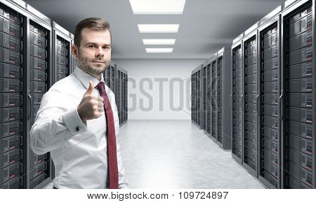 Man With His Right Thumb Up In Server Room For Data Storage, Processing And Analysis, Two Rows Of Ma