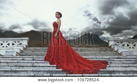 Beautiful young woman in long red dress