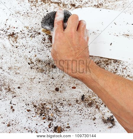 Hand with wet sponge cleans very dirty surface