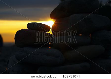 Ray of the setting sun streaming through the rocks on beach