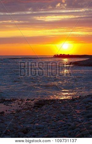 Beautiful sea sunset on stony seashore