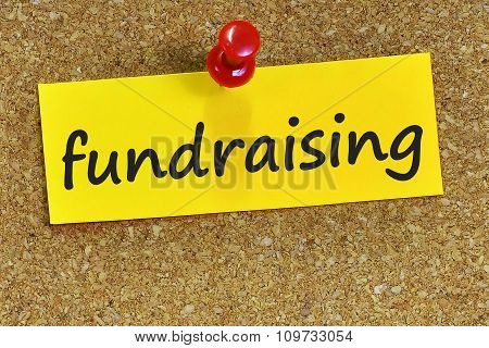 Fundraising Word On Yellow Notepaper With Cork Background