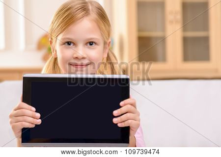 Joyful little girl holding tablet