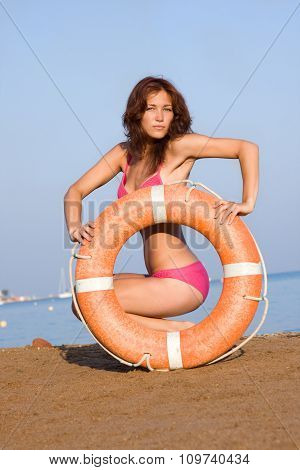 A young girl on the beach with a Life Ring