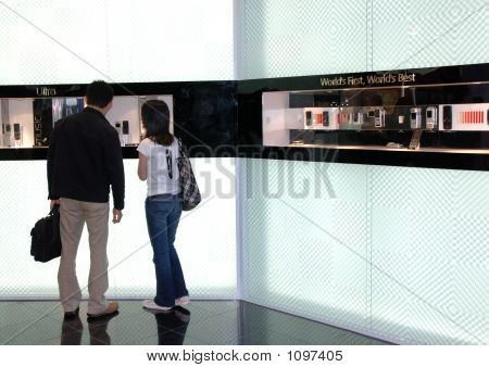 People Watching New Mobile Display In Telecom Exhibition