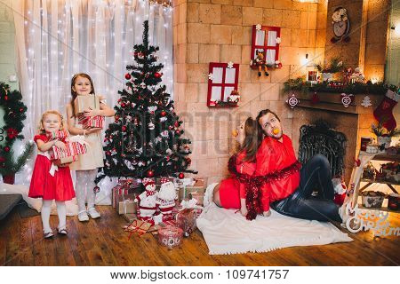 Happy Family Sitting Near Christmas Tree.  in red hat