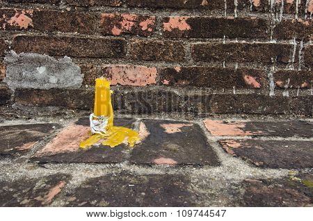 Yellow candle in front of brown brick wall