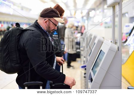 GENEVA, SWITZERLAND - NOVEMBER 19, 2015: passenger use self-registration kiosk in Geneva Airport. Geneva International Airport is the international airport of Geneva, Switzerland.