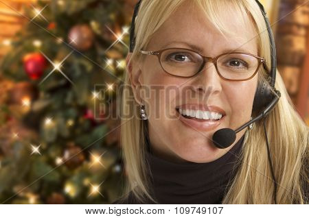Happy Woman with Phone Headset In Front of Christmas Tree.