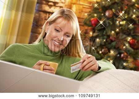 Beautiful Woman Using Her Credit Card In Front of Christmas Tree and Laptop Computer.