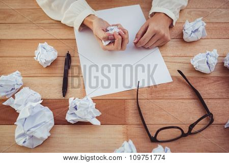 Cropped image of woman with crumpled paper in her office