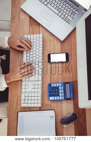 Cropped image of woman typing on keyboard in her office