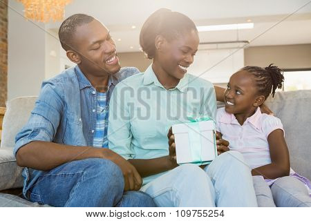 Pretty couple offer a present for their daughter in living room