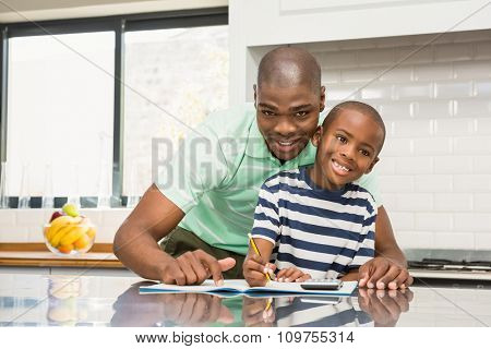 Father helping his son with homework in the kitchen