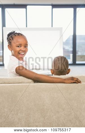 Two children sitting on sofa in living room