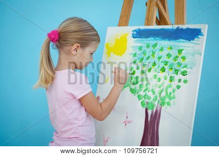 Happy girl painting her picture on an easel