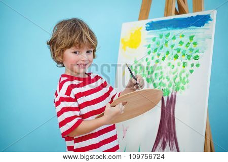 Happy boy painting his picture on an easel