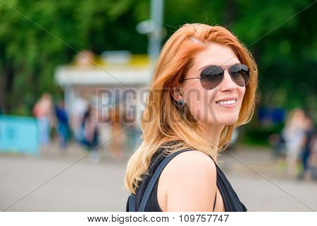 Smiling Stylish Girl In Sunglasses In A City Park