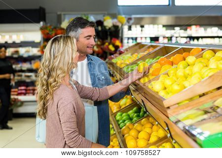 Happy smiling couple picking orange at supermarket