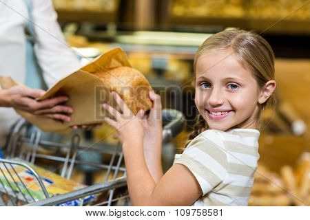 Daughter taking bread from paper bag in supermarket