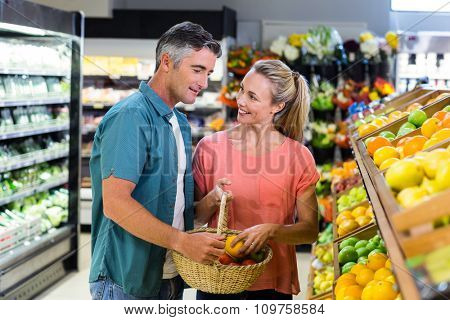 Happy couple putting apple in the basket and talking