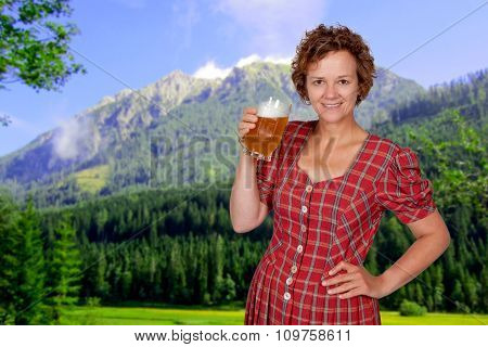 Mid age smiling woman holding a beer in her hands