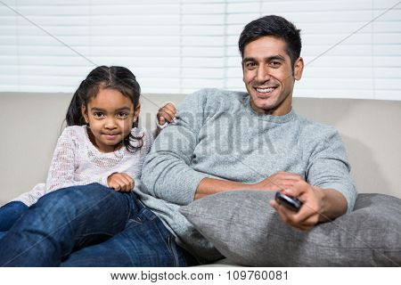 Smiling father watching tv with daughter on the sofa in living room
